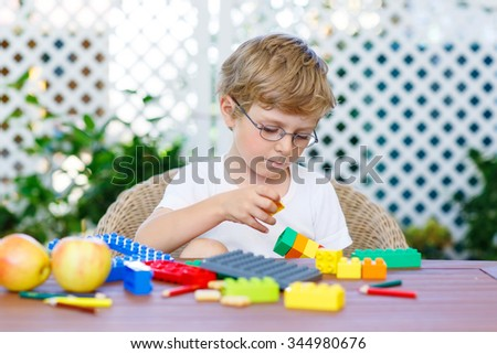 Beautiful blond child with glasses playing with lots of colorful plastic blocks indoor. Active kid boy having fun with building and creating. - stock photo