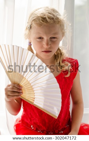 beautiful blond child with long hair in red dress among white curtain - stock photo