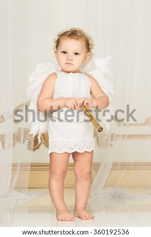 Beautiful blond curly toddler in a white lace dress with wings as a Cupid playing with his flute in the white room with gold moldings in baroque style. Saint Valentines Day