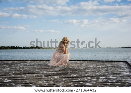 Beautiful blond curly woman wearing evening peach color gown squatted on the deck at the lake. Fashionable and glamorous dress and style.