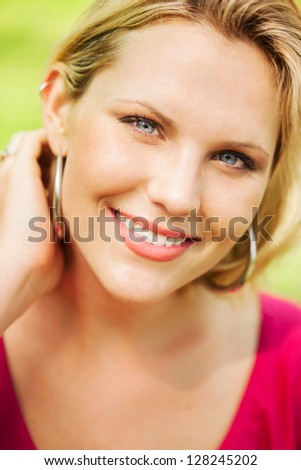 Beautiful blond early 30s woman head shot portrait outdoors sweeping hair back with hand - stock photo