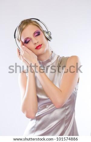 Beautiful blond electro pop gir enjoying music in headphones. - stock photo