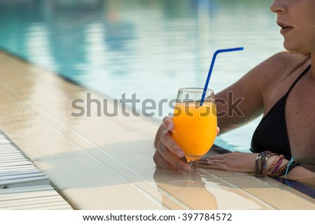 Beautiful blond enjoying on a swimming pool, drinking an orange juice - stock photo