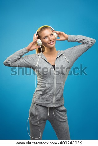 Beautiful blond fit caucasian lady in grey sport  with headphones listening music. Isolated on blue background. - stock photo