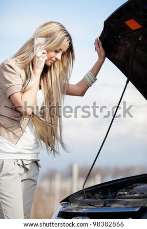Beautiful blond girl calling cellphone near her broken car - stock photo