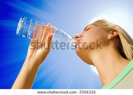 Beautiful blond girl drinking water - stock photo