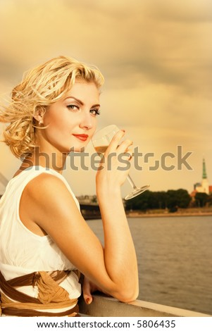 Beautiful blond girl drinks champagne near the river at sunset time - stock photo