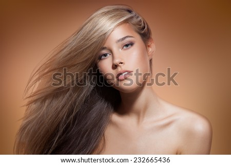 Beautiful Blond Girl. Healthy Long Hair. Brown Background - stock photo