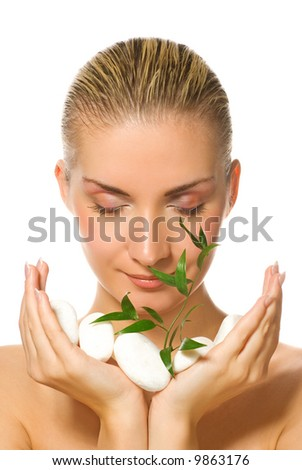 Beautiful blond girl holding young plant growing up through stones - stock photo