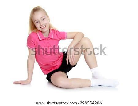 Beautiful blond girl in a pink shirt and short black shorts sitting on the floor leaning on your hand, a sweet smile on her face-Isolated on white background - stock photo