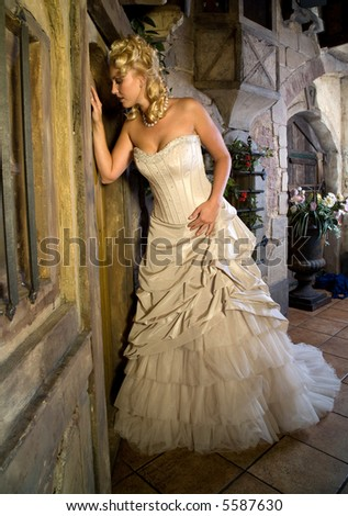 Beautiful blond girl in gorgeous wedding dress peeking through the window of the doos