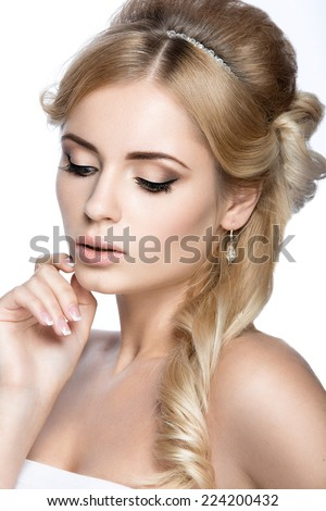 Beautiful blond girl in the image of a bride with a tiara in her hair. Picture taken in the studio on a white background. - stock photo
