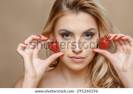 Beautiful blond girl is raising two strawberries to her cheeks. She is looking at the camera with temptation. Isolated on brown background - stock photo