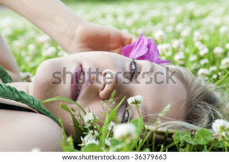 beautiful blond girl lying down of grass