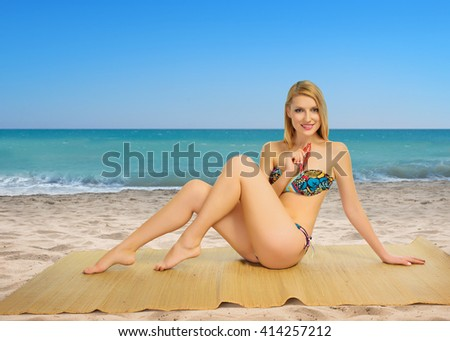 Beautiful blond girl on the beach in summer - stock photo