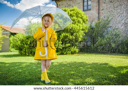 Beautiful blond girl plays with the rainy weather.