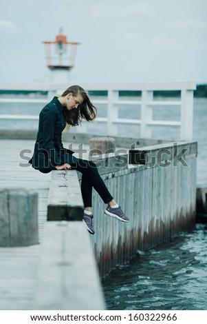 Beautiful blond girl sits on pier - stock photo