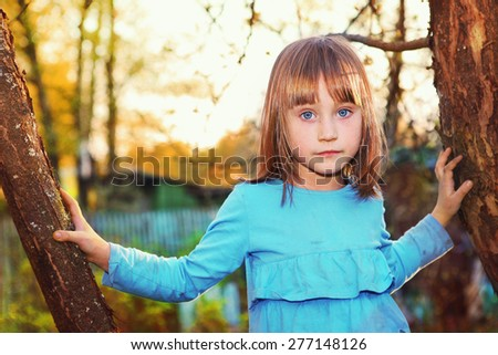 beautiful blond girl with blue eyes climb old tree in the spring country garden at sunset time - stock photo