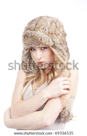 beautiful blond girl with blue eyes in fur hat - isolated on white - stock photo