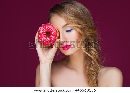 Beautiful blond girl with colorful doughnut - stock photo
