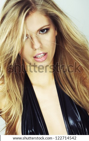 Beautiful blond girl with hair fluttering in the wind - stock photo