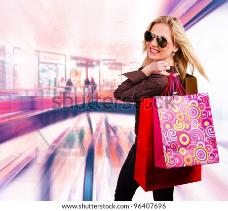 Beautiful blond girl with shopping bags - stock photo