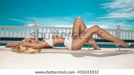 Beautiful blond hair sexy woman young girl model in  elegant white sexy swimsuit with crystals around the pool with a balustrade overlooking the sea and the Santorini Island - stock photo