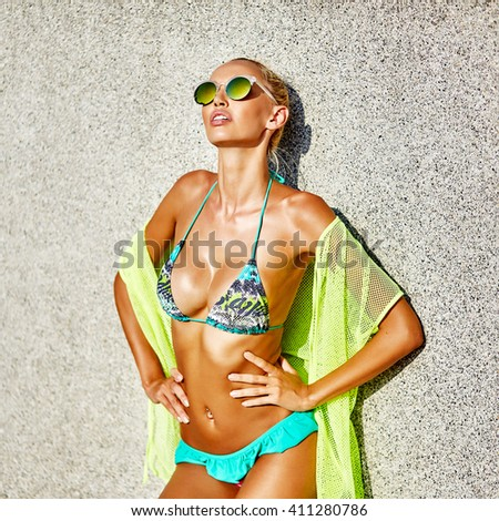 Beautiful blond hair sexy woman young girl model in sunglasses and elegant sexy swimsuit  - stock photo