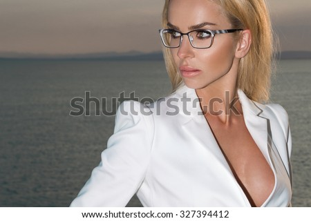 Beautiful blond hair sexy woman young girl model in sunglasses in white dress, elegant jacket with crystals around the pool with a balustrade overlooking the sea and the island of Santorini