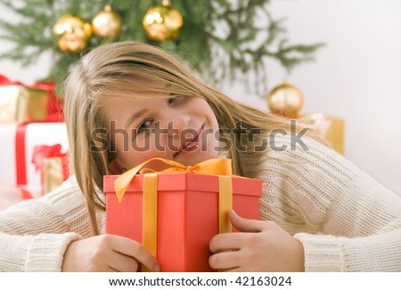 Beautiful blond hair teenage girl in white sweater holding red gift box with golden ribbon. Fir tree with golden glass-balls in background. - stock photo