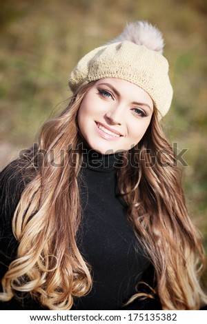 Beautiful blond hair woman standing and posing at the park - stock photo