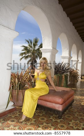 Beautiful Blond holding a Wine glass sitting in front of arches. - stock photo