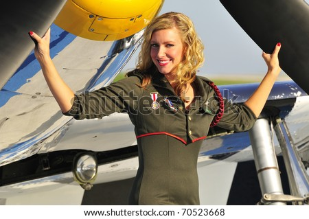 beautiful blond in an army uniform standing in front of a fighter plane - stock photo