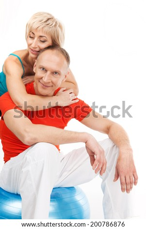 beautiful blond lady hugging aged man. male sitting on fitness ball and smiling - stock photo