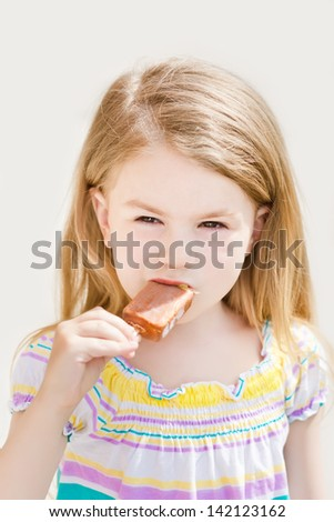 Beautiful blond little girl with long hair eating ice-cream in summer sunny day