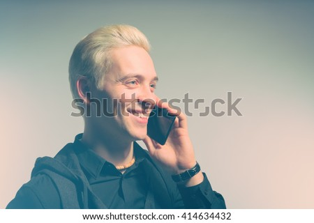 Beautiful blond man dressed in black talking on the phone. Toned