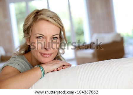 Beautiful blond mature woman relaxing in sofa - stock photo