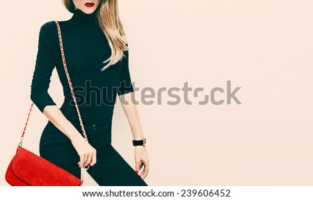 Beautiful blond model classic black style with red fashionable clutch - stock photo