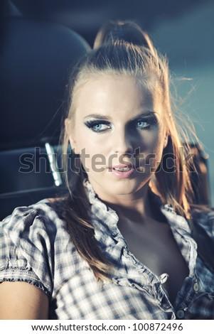 Beautiful blond model sitting on old car at night shot - stock photo
