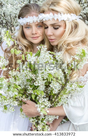 beautiful blond mother with a daughter, little princess, hug and smile, in your hand,  they keep white flowers  in the garden among white flowers, dressed in white wedding, ethereal communion dresses - stock photo