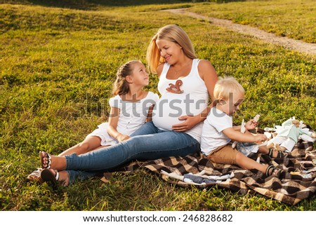 Beautiful blond pregnant woman enjoying her older kids company. Mother with kids outdoors in sunlight. Mother's day concept - stock photo