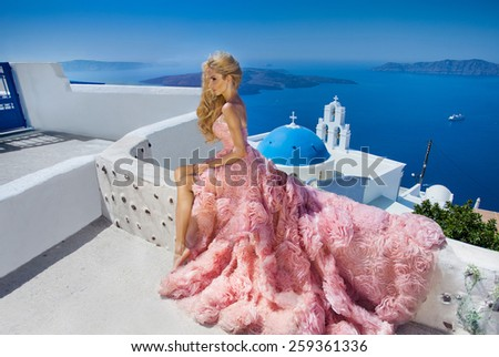 Beautiful blond runaway bride in white wedding dress fabulous with a very long train of crystals in the street on Santorini in Greece. - stock photo