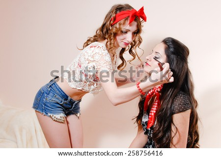 Beautiful blond sexy girl with brush drawing make up to her brunette friend with red lipstick - stock photo