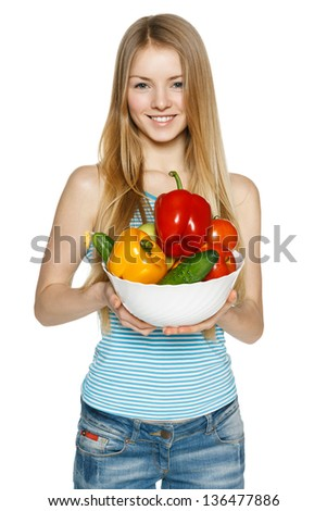 Beautiful blond smiling girl holding bowl with vegetables (sweet pepper red and yellow, cucumber, tomato) over white background