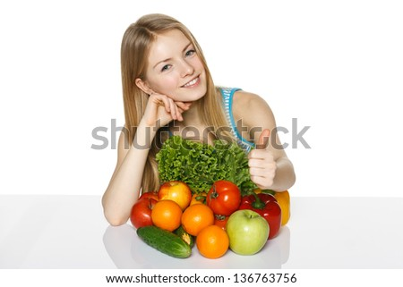 Beautiful blond smiling girl sitting with vegetables and fruits  on table, showing thumb up gesture, over white background