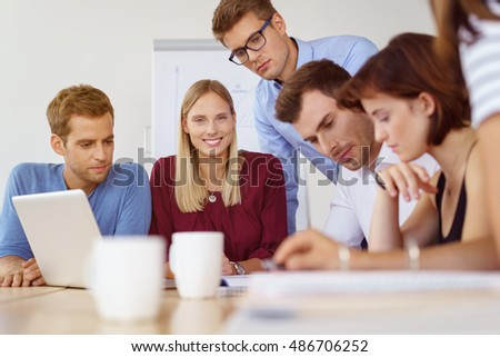 Beautiful blond smiling woman and colleagues seated at conference table during meeting discussing reports