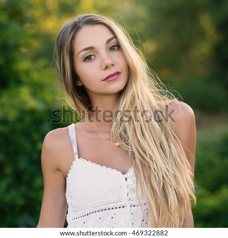 Beautiful blond teenager portrait outdoors in the park. Filtered image.