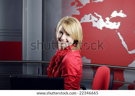 Beautiful blond Television Presenter in front of the laptop looking at the camera - stock photo