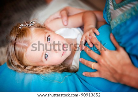 Beautiful blond toddler girl smiling and holding belly of her pregnant mother - stock photo