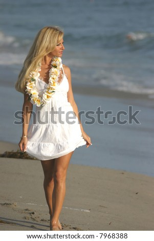 Beautiful Blond walking on the beach in a White dress and a Lei at Sunset